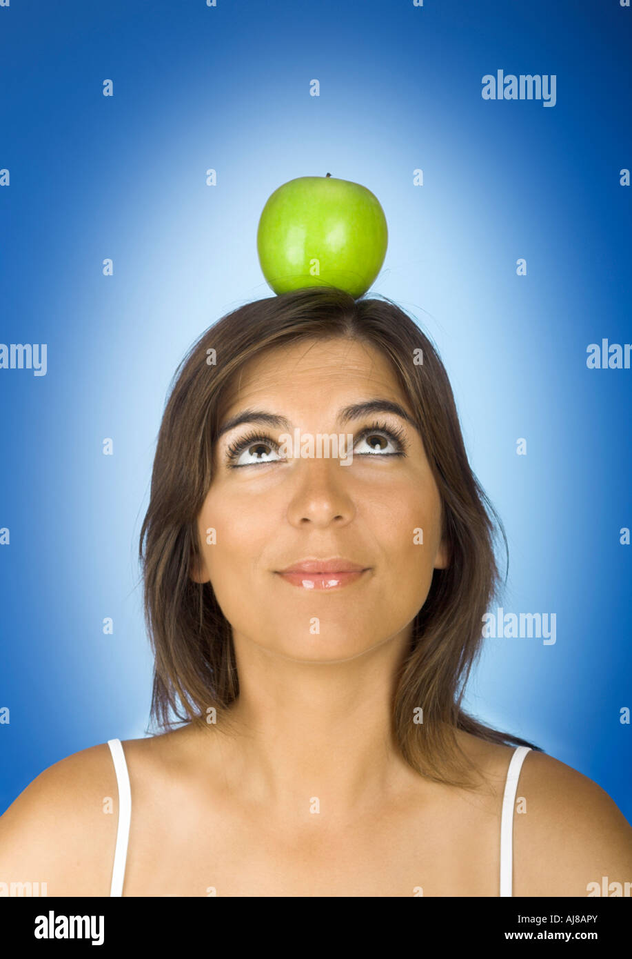 Portrait of a young woman with a apple on the head - Stock Image