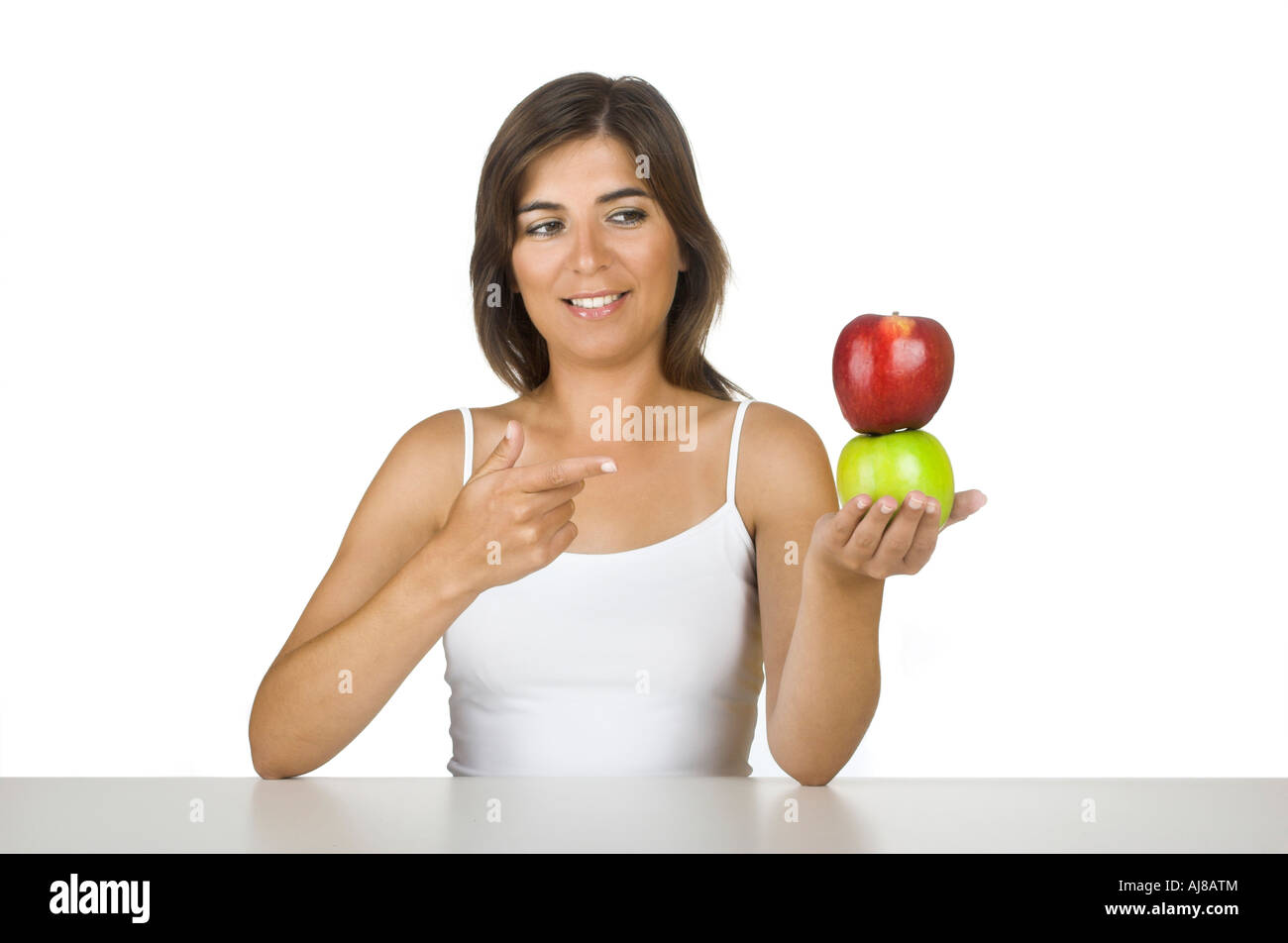 Beautiful young woman holding a green and a red apple - Stock Image