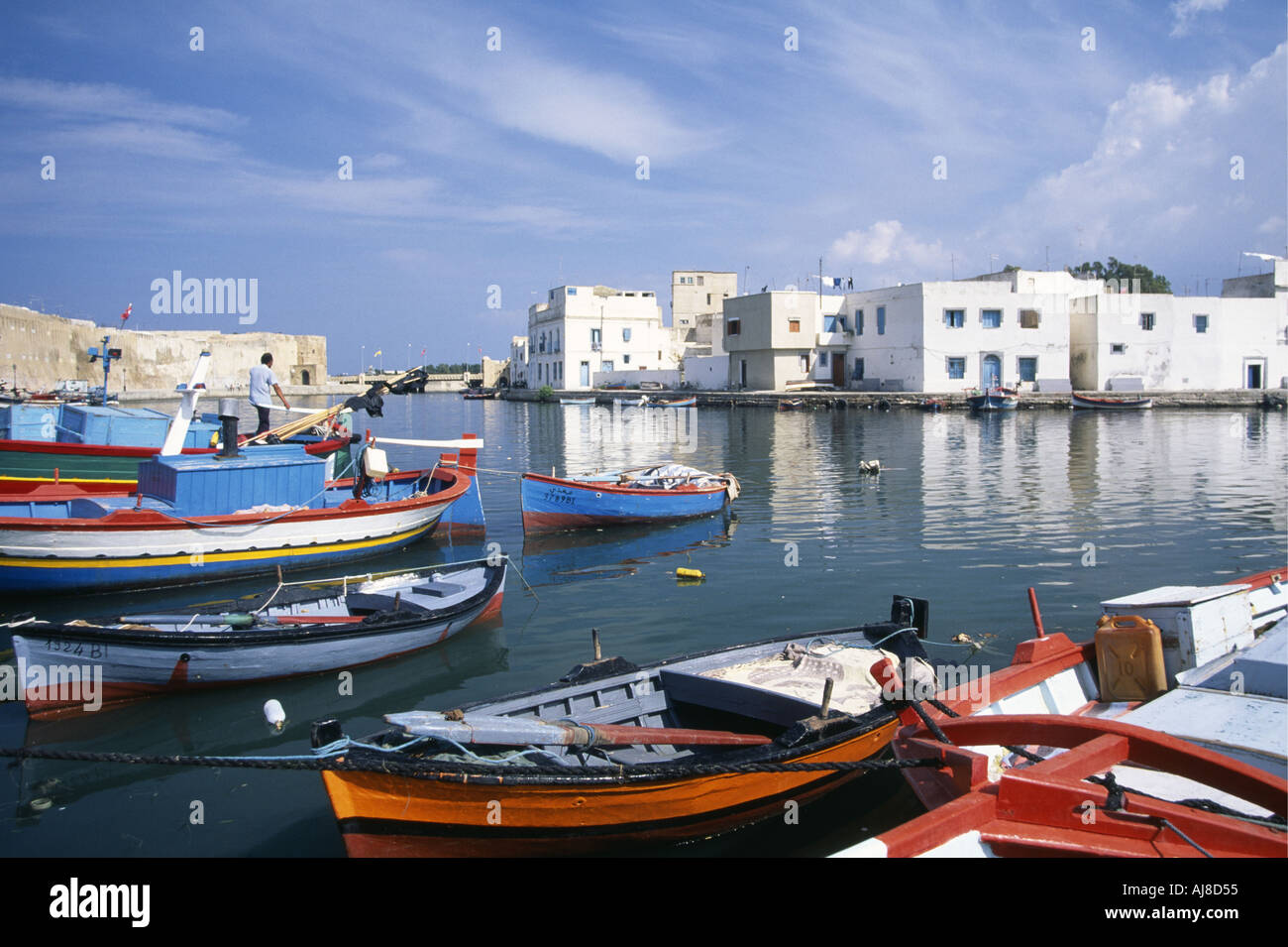 A man on the deck of a small boat of the fishing fleet tied up in the old corsair harbour at Bizerte encircled by the blue and white houses of the medina adjacent to the yellow stone walls of the kasbah Tunisia - Stock Image