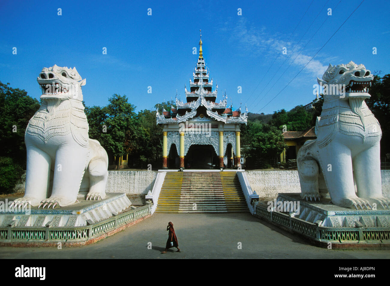 Monk walks by Lions Foot of Mandalay Hill Steps in Mandalay located in Myanmar Burma - Stock Image