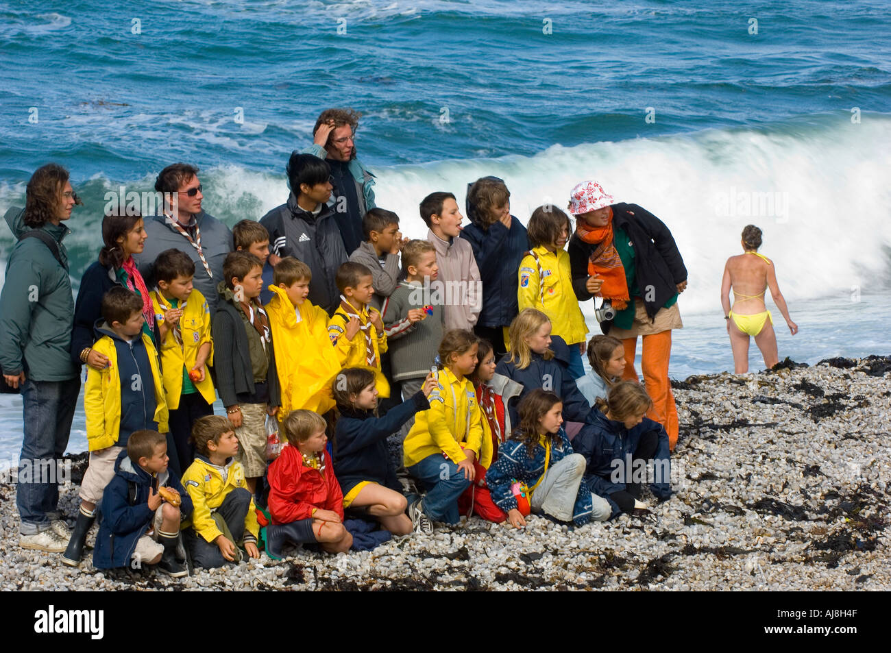 French schoolchildren pose for a photograph in warm clothing on Etretat beach while a woman bathes in a bikini - Stock Image