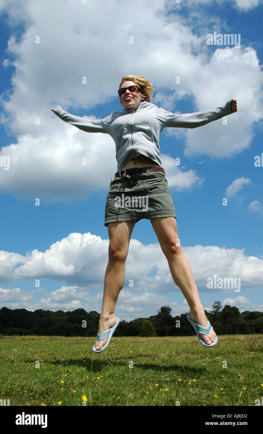 Girl star jumping - Stock Image