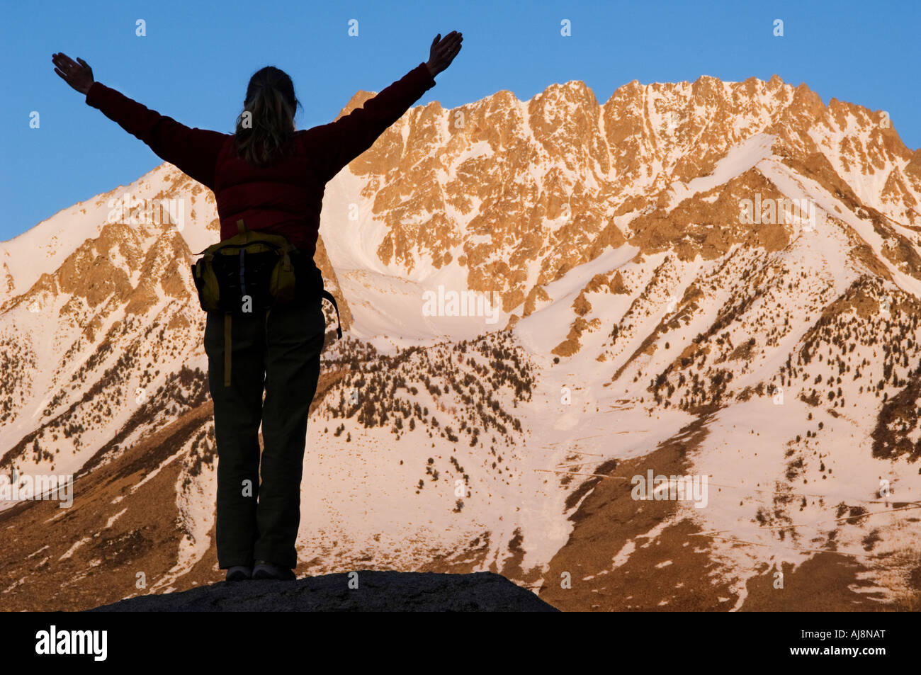 Hiker watches the sun rise. - Stock Image