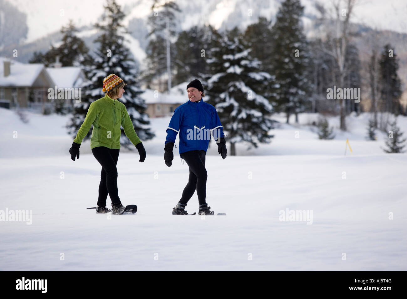 Middle-aged couple snowshoeing at Fernie, British Columbia, Canada. - Stock Image