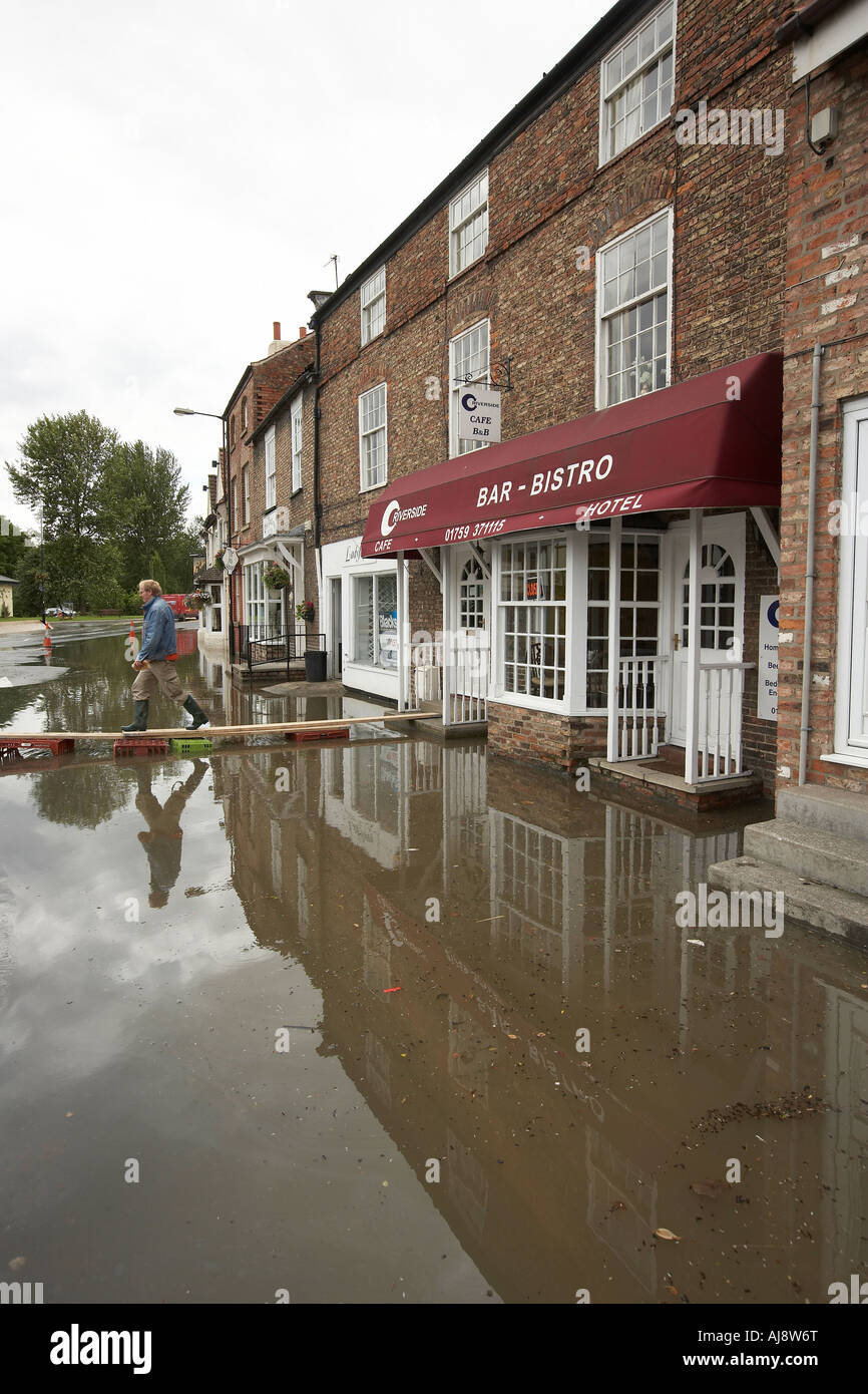 Shopper walking on platform over flood water to reach shops in Stamford Bridge East Yorkshire UK June 2007 - Stock Image