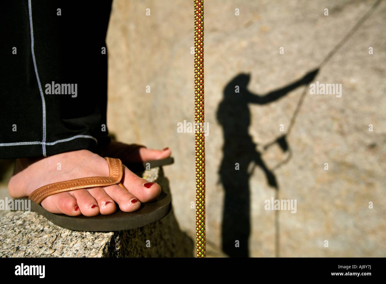 Female belay shadow on rock - Stock Image