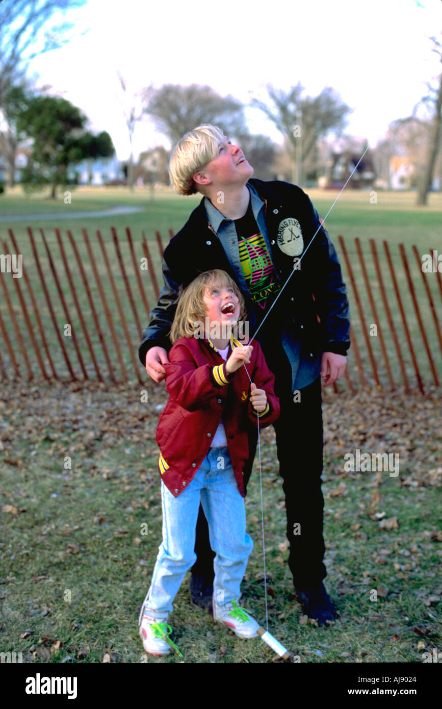 Cousins age 16 and 7 flying kite at Easter family gathering. Victory Memorial Drive Minneapolis Minnesota USA - Stock Image