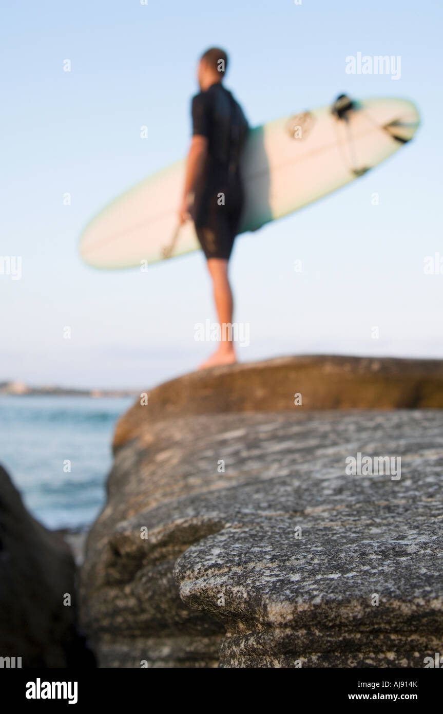 Surfer with board watches ocean. - Stock Image