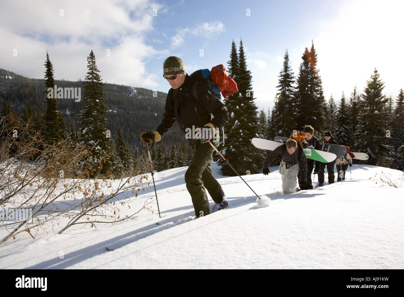 Skiers and snowboarders climb uphill - Stock Image
