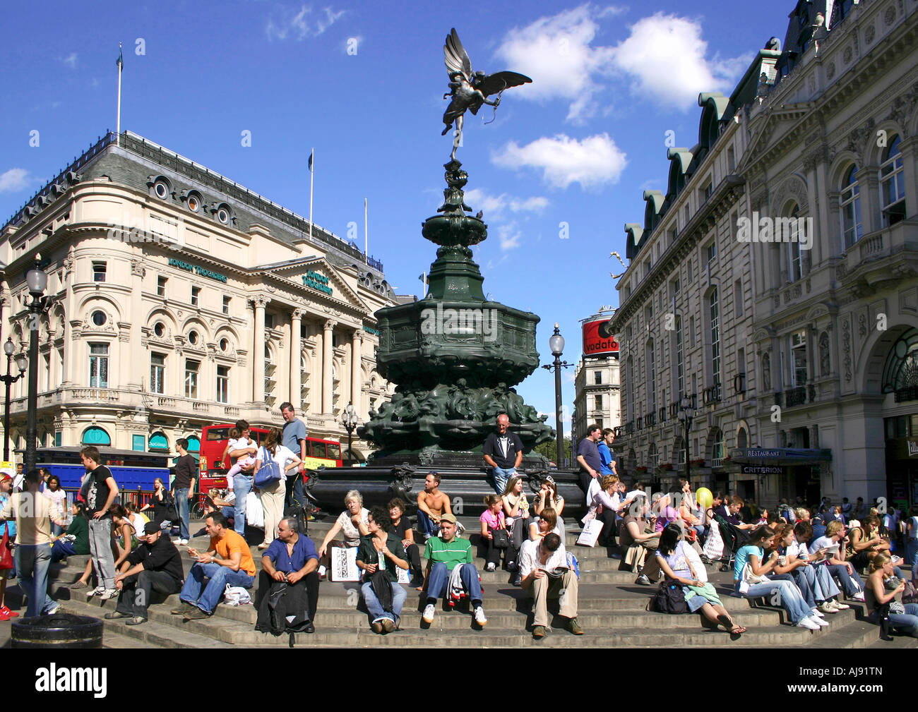 Tourists sitting by the statue of Eros, piccadilly Circus, London, England - Stock Image