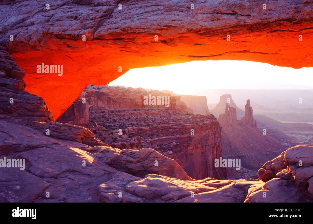 Dawn sun lights the underside of Mesa Arch, Canyonlands National Park, Utah, USA - Stock Image