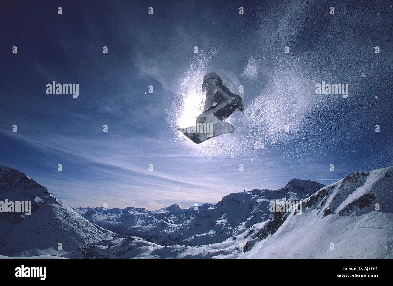 Snowboarder flies into the sun in Les Arcs French Alps - Stock Image