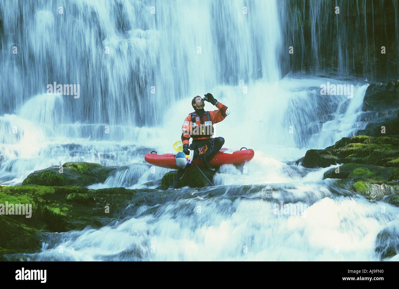 Shaun Baker rehydrating during an extreme kayaking shoot - Stock Image
