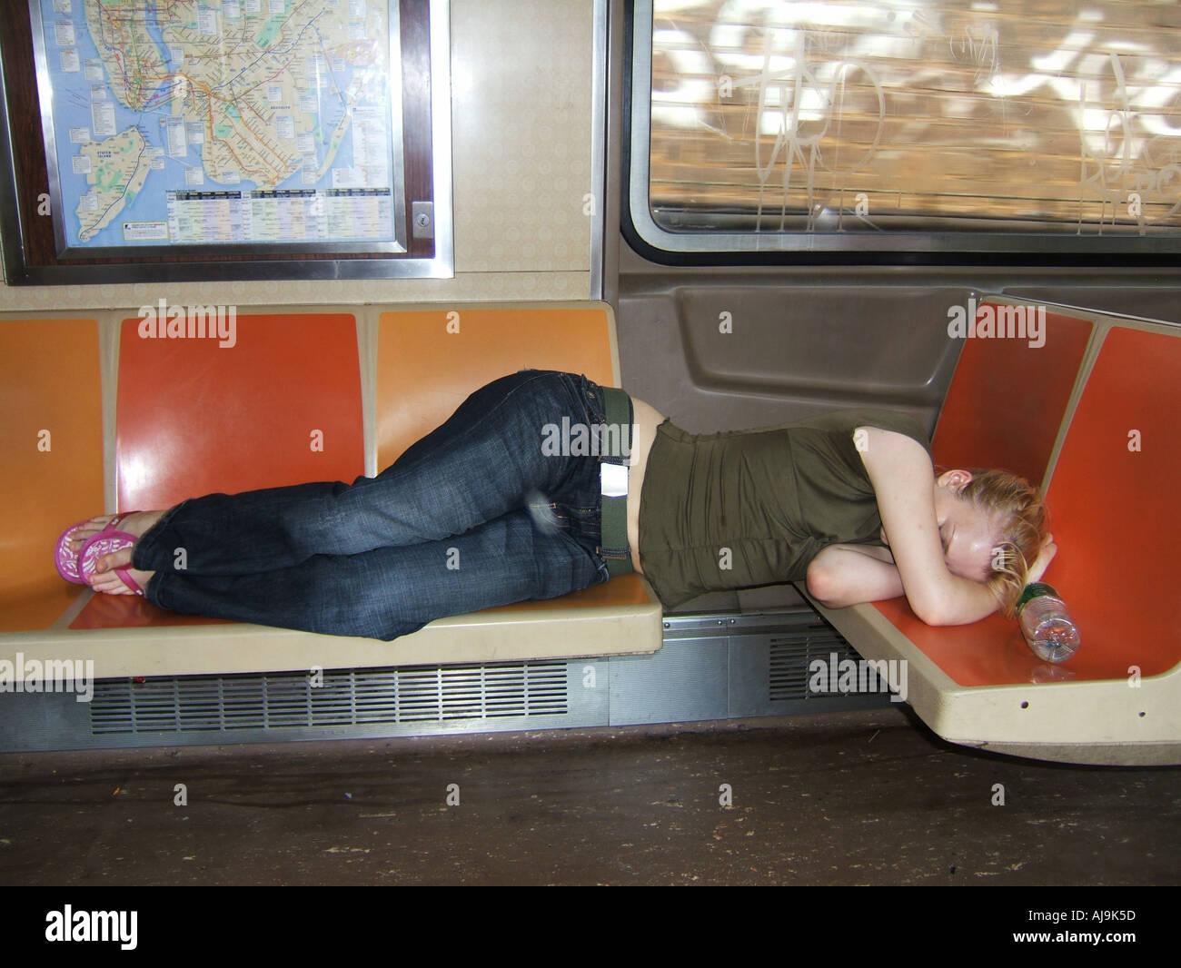 Girl lying on seat below subway map New York subway train manhattan USA Stock Photo