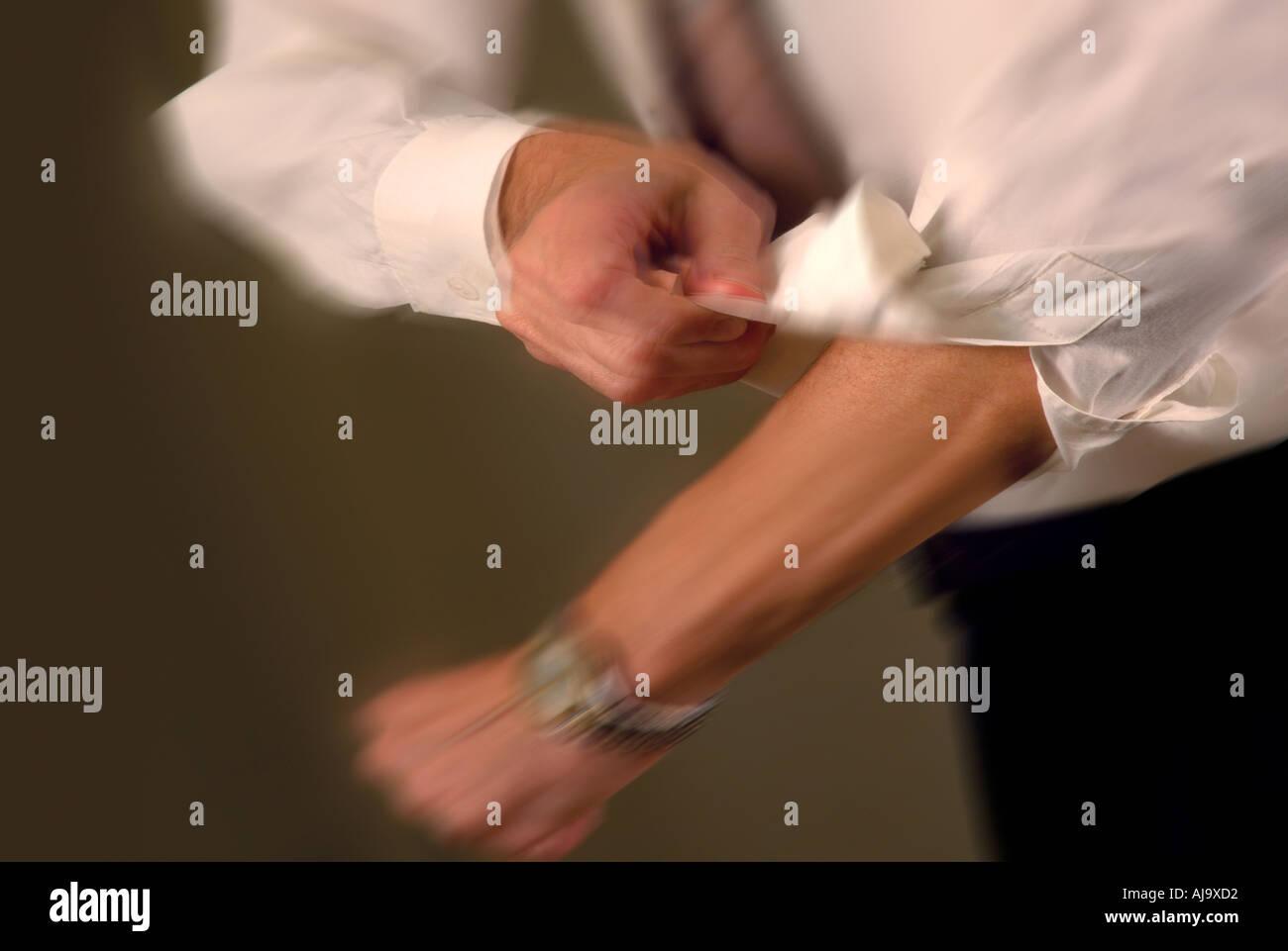 businessman rolling up shirt sleeve - Stock Image