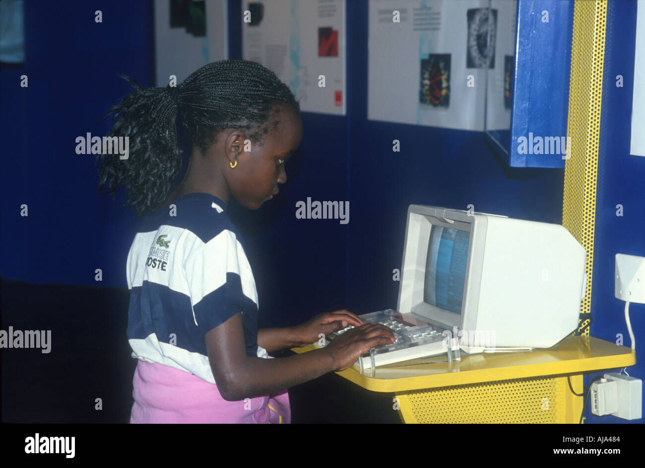 young colored coulered girl about ten years old sitting a working at a little personal computer  - Stock Image