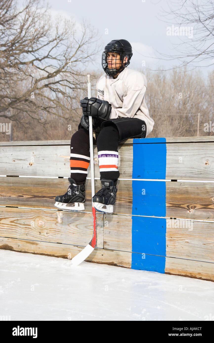 Boy in ice hockey uniform holding hockey stick sitting on sidelines - Stock Image