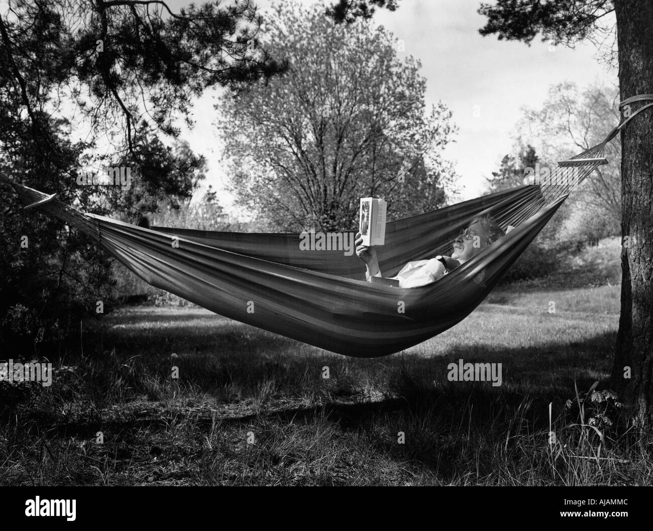 Old gentleman lies back in a hammock reading good books - Stock Image