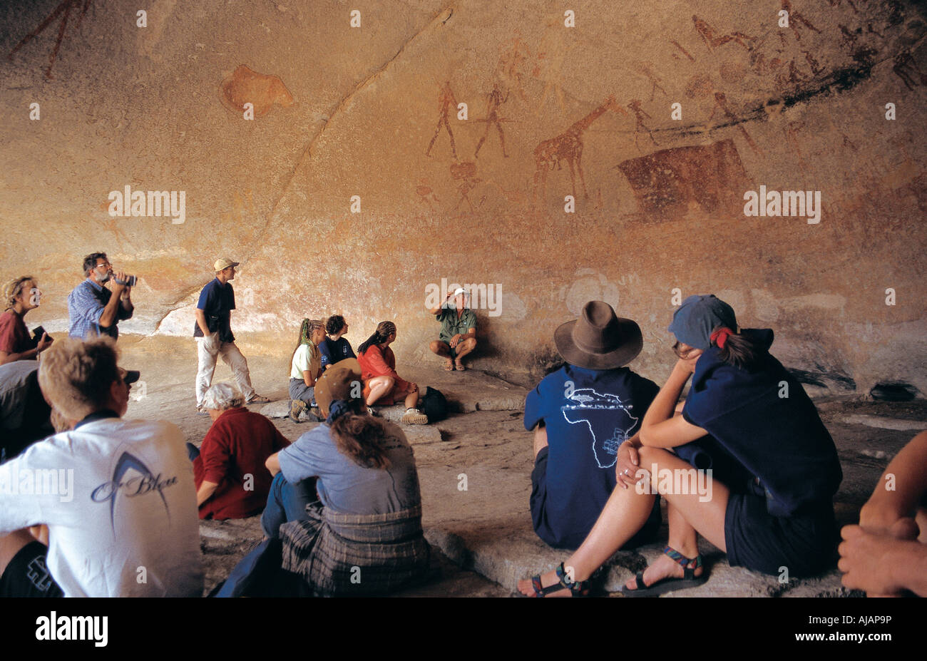 Guide Ian Harmer gives lecture on Bushman paintings inside a cave in Matobo National Park Zimbabwe Stock Photo