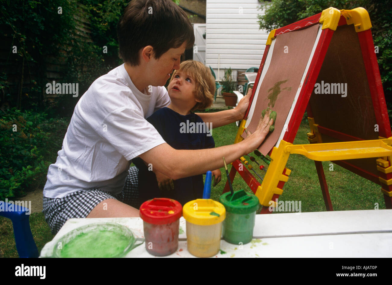 An infant looks into her mother's face while painting art with her mum on an easel in their back garden in South Stock Photo
