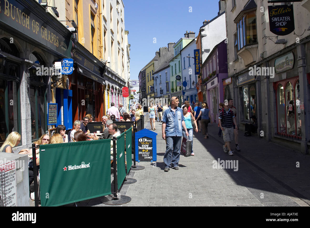 pedestrians and drinkers enjoying a sunday afternoon drink in the bunch of grapes pub high street - Stock Image