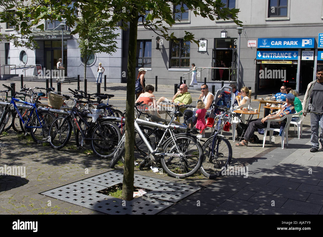 familes enjoying a drink and lunch on quay street next to a bike rack Galway city county Galway Republic of Ireland - Stock Image