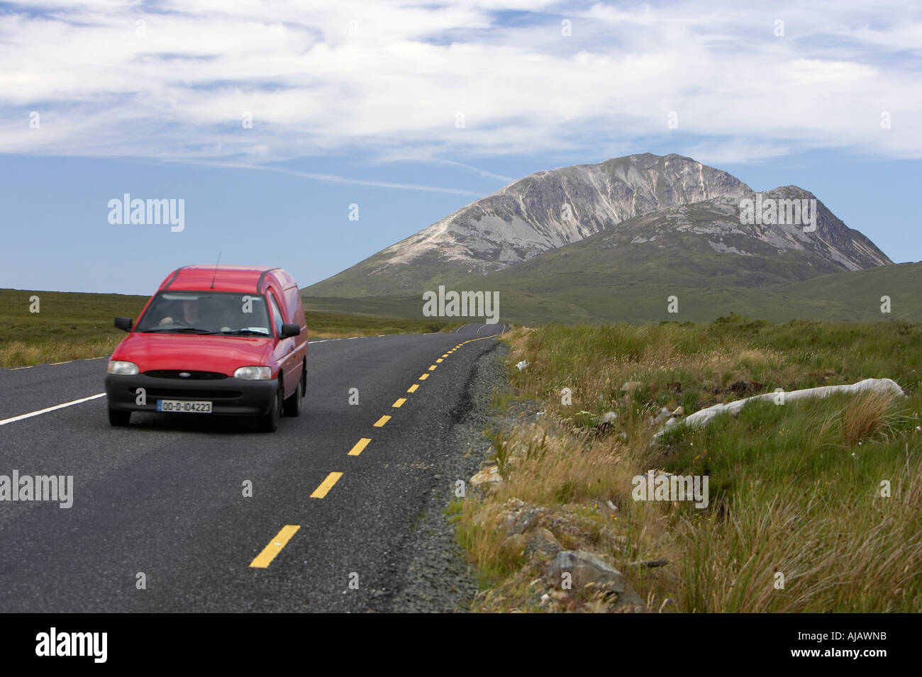red van on road at Errigal mountain donegals highest peak against a blue sky between dunlewey and letterkenny - Stock Image
