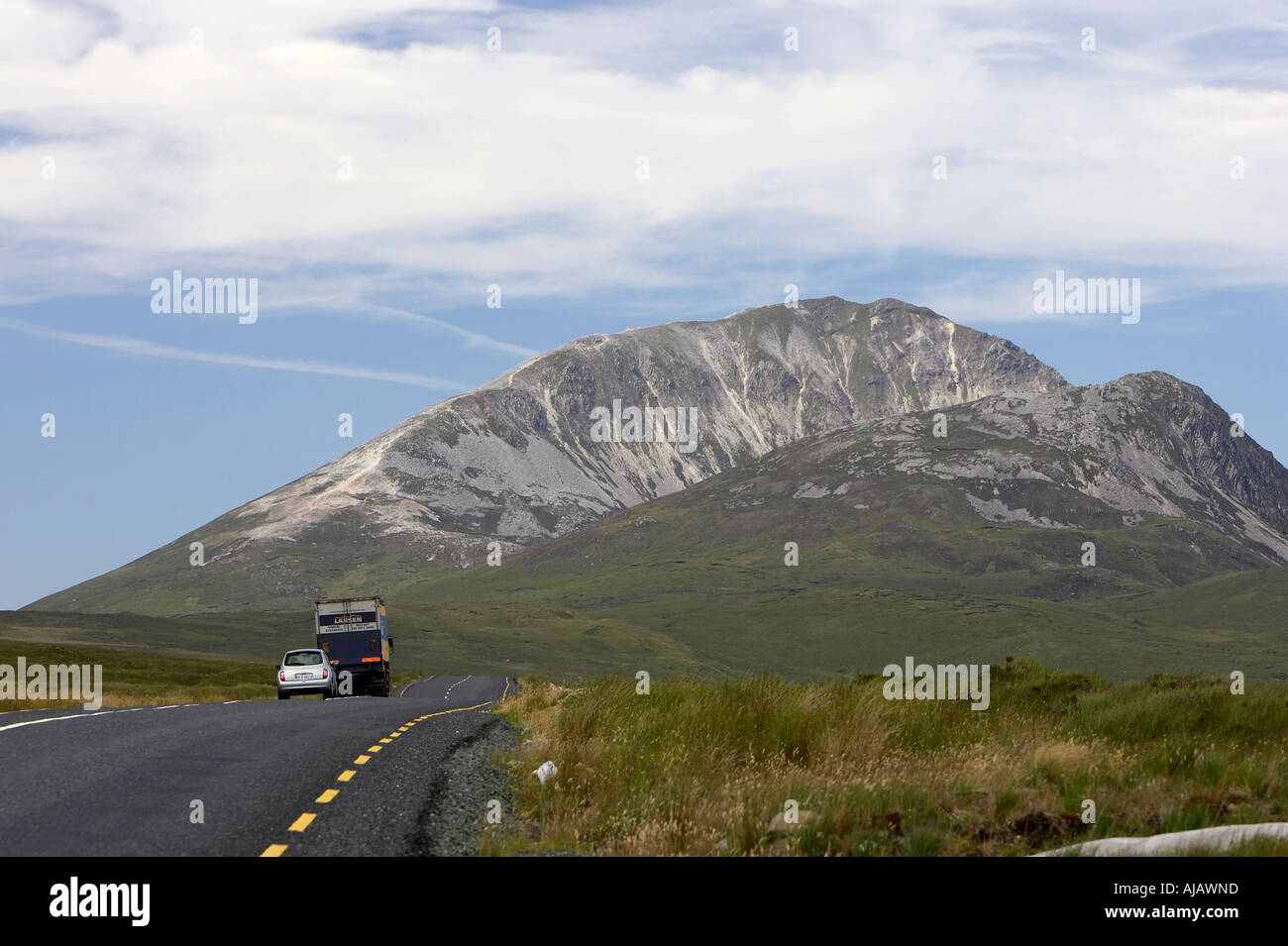 cars on road to Errigal mountain donegals highest peak against a blue sky between dunlewey and letterkenny - Stock Image