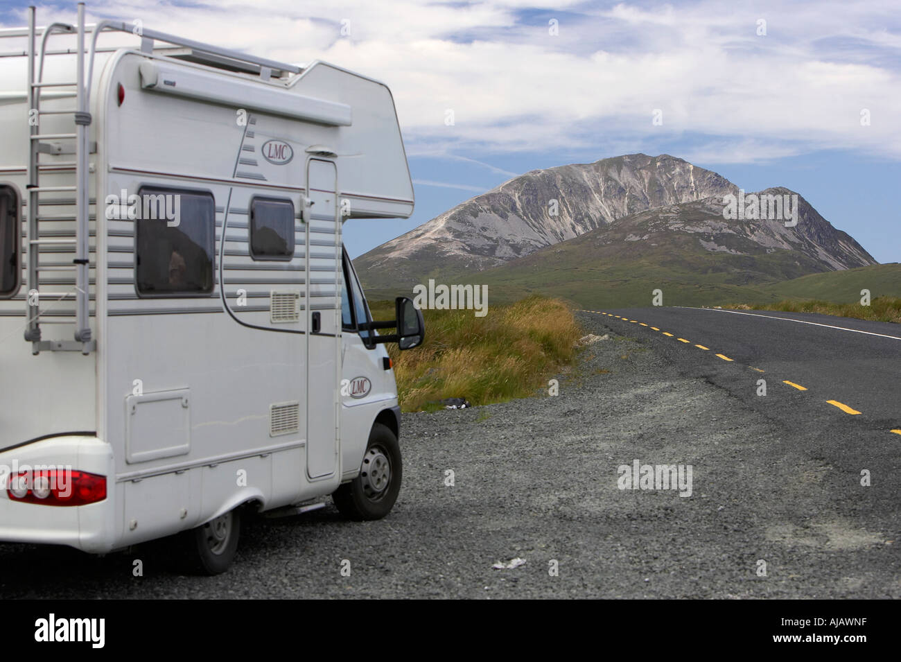 touring camper van at the side of the road next to Errigal mountain donegals highest peak against a blue sky - Stock Image