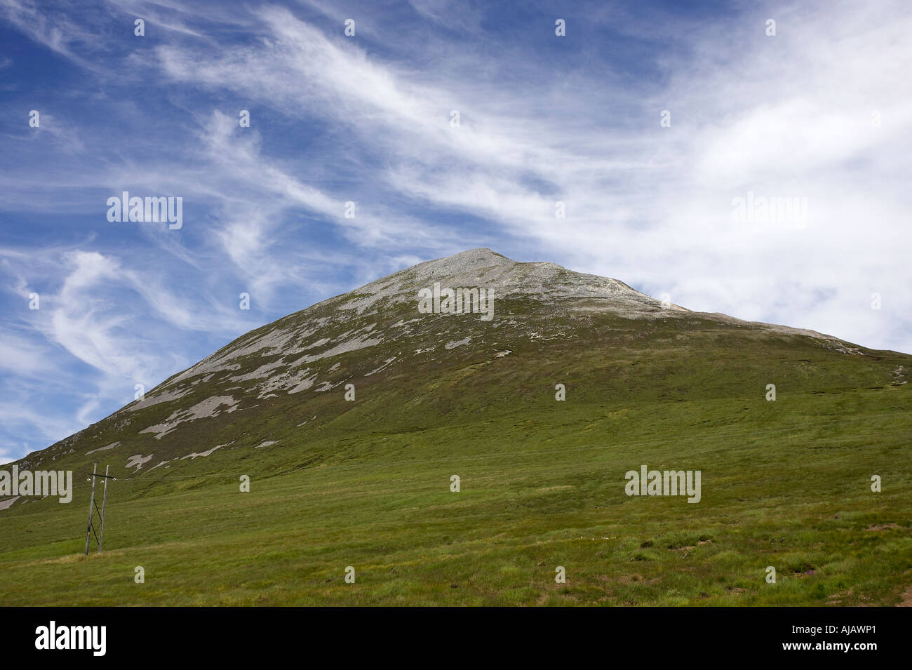 peat bog and summit of Errigal mountain donegals highest peak against a blue sky between dunlewey and gweedore - Stock Image