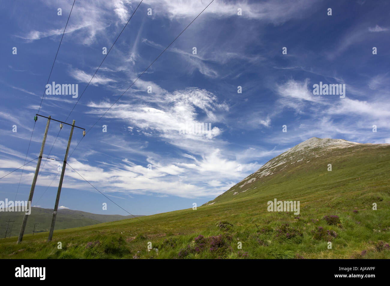 electricity poles and lines at Errigal mountain donegals highest peak against a blue sky between dunlewey and gweedore - Stock Image