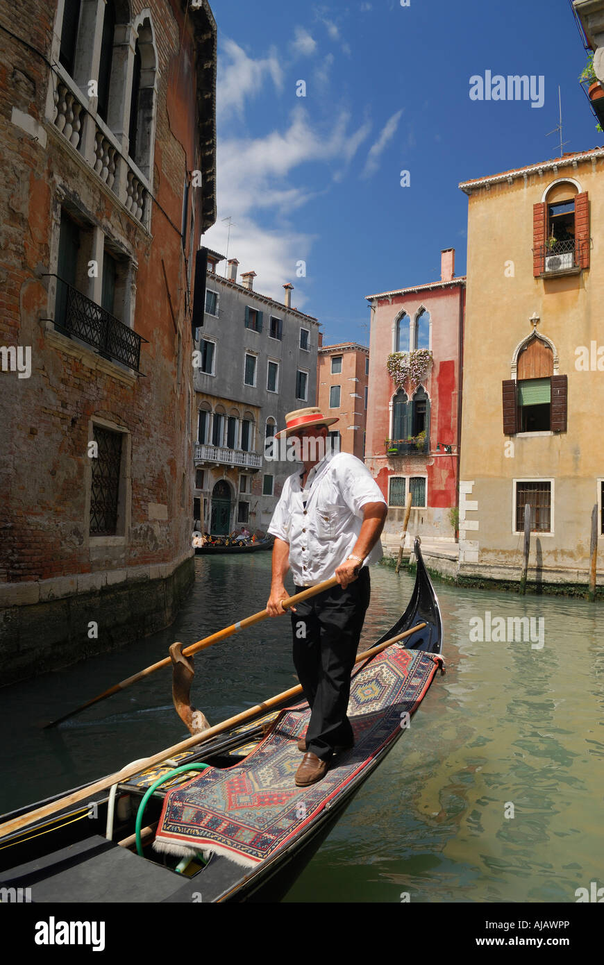 Gondolier plying his trade on a canal in Venice - Stock Image
