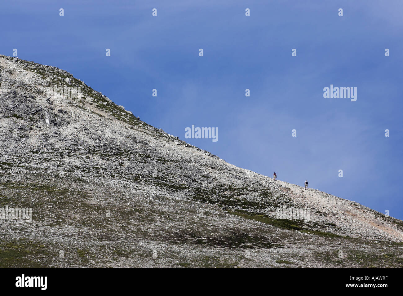 climbers walking along ridge of Errigal mountain donegals highest peak against a blue sky - Stock Image