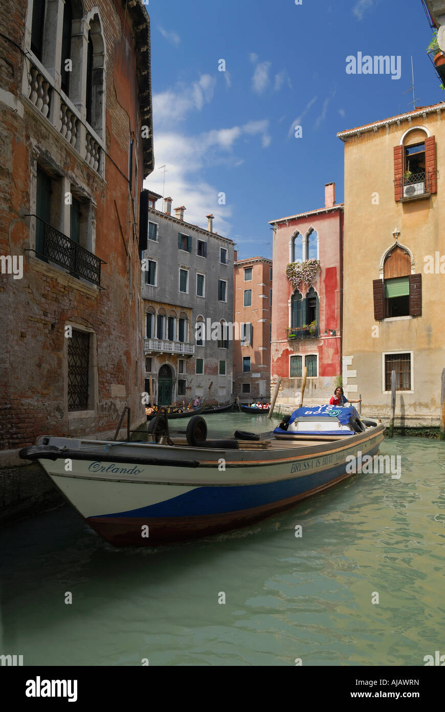 Riverboat plying the narrow waters of a canal in Venice - Stock Image