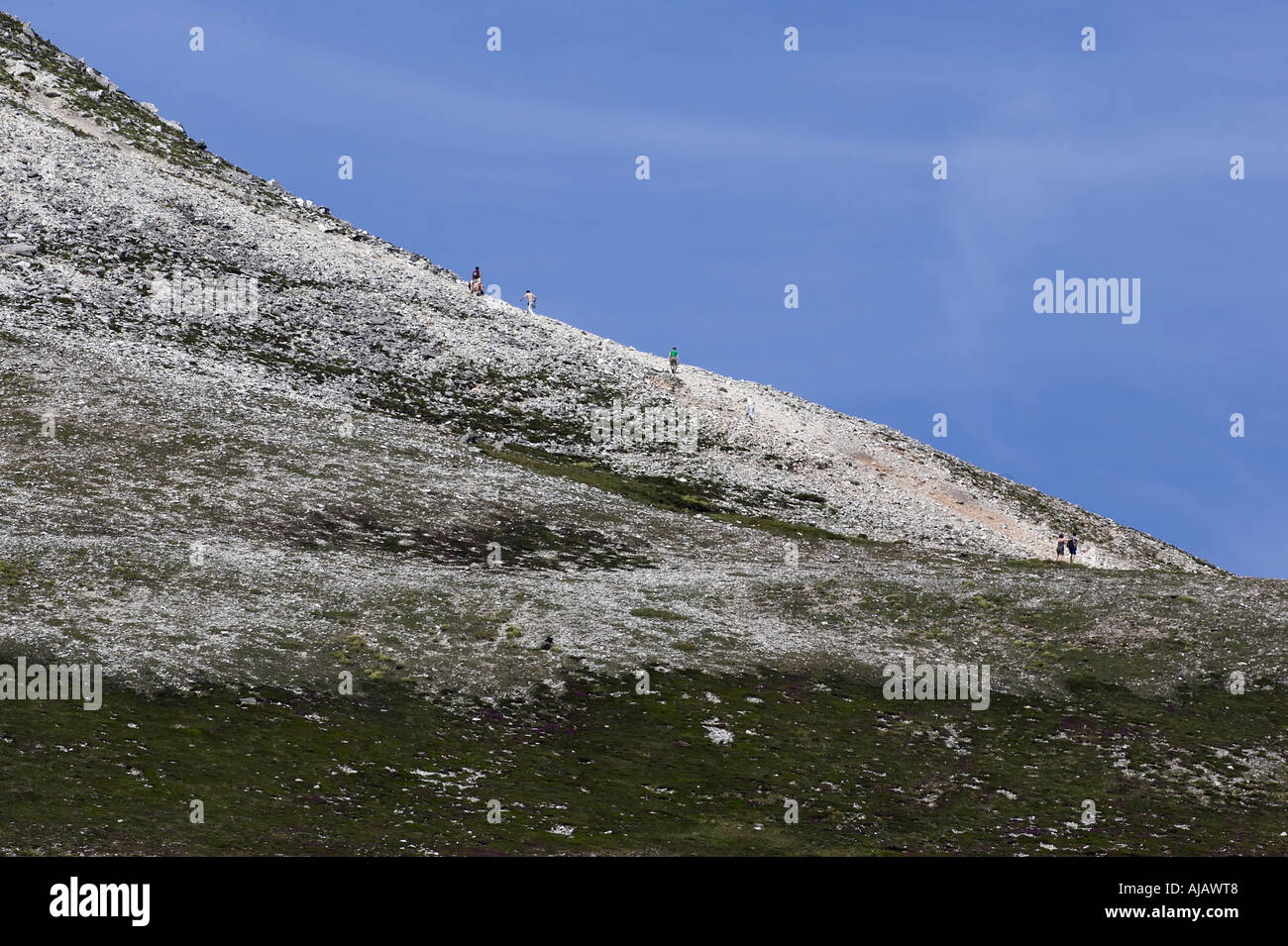 climbers climbing ridge on Errigal mountain donegals highest peak against a blue sky - Stock Image