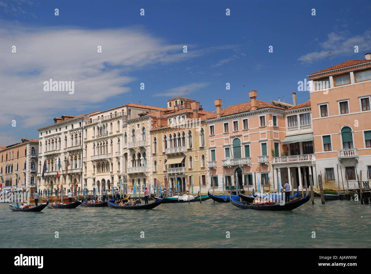 Row of stucco houses and gondoliers plying the Grand Canal in Venice Italy - Stock Image