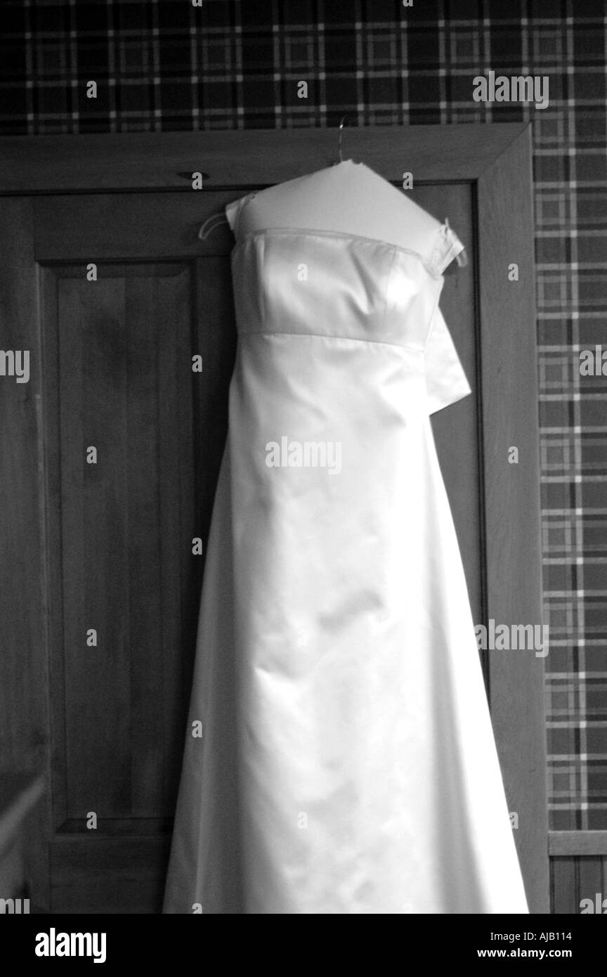 Black and white image of wedding dress hanging on the door frame ...