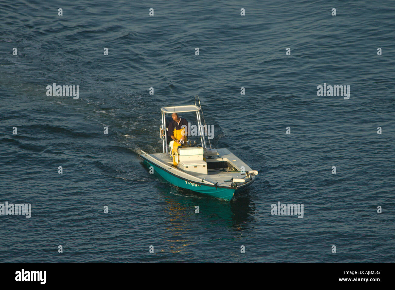 Boating power outboard motor boat commercial fisherman cruises in calm flat  water, yellow waders, casting platform