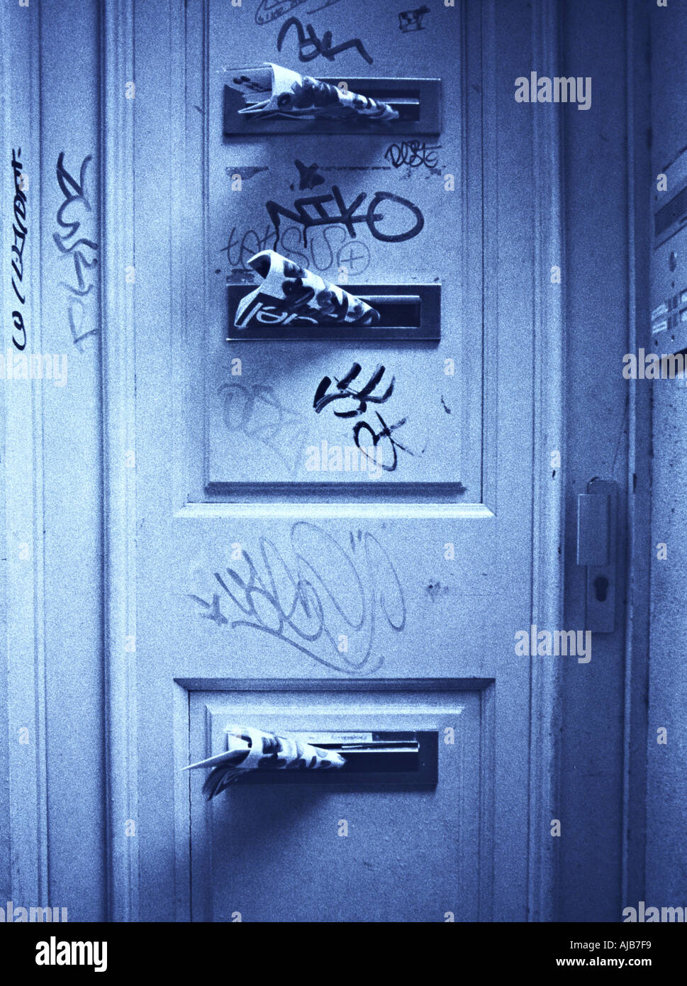 Werbung in Briefkästen einer Graffiti Tür advertising in post boxes at a door with graffiti - Stock Image