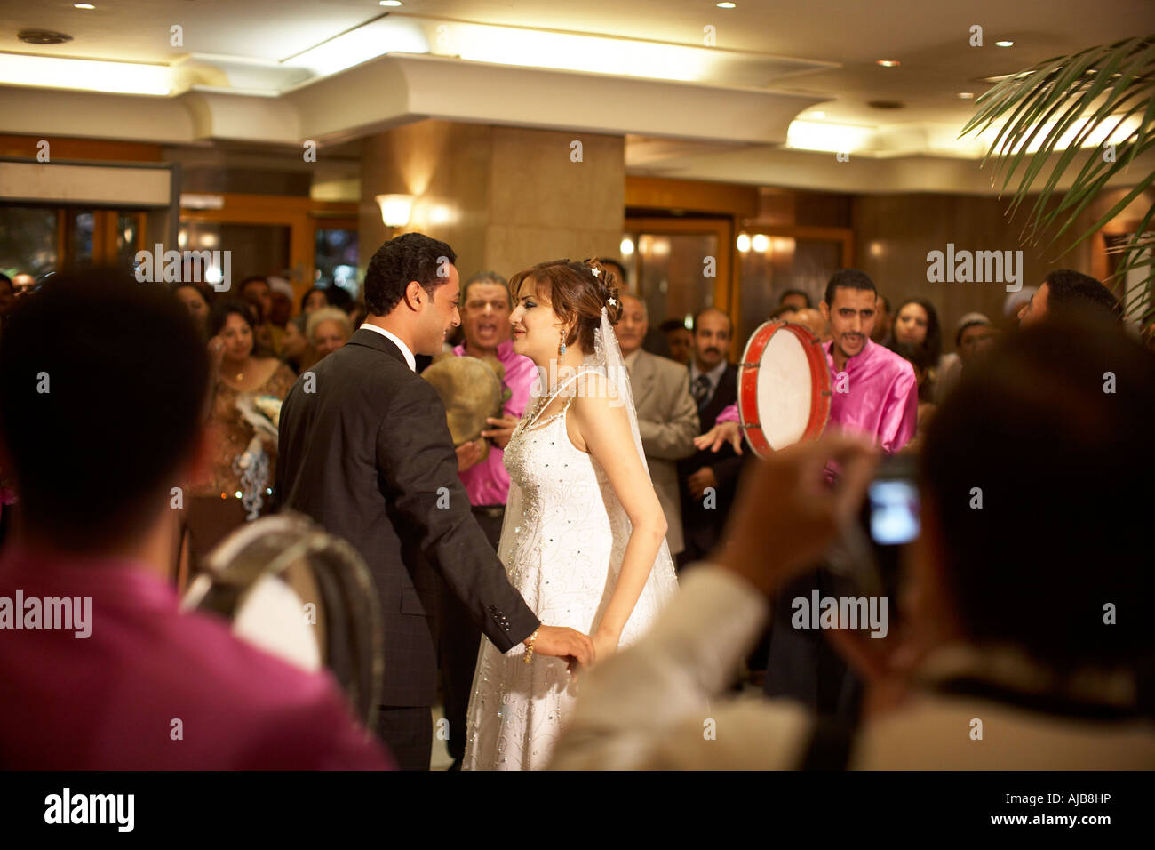 Bride Groom and wedding guests at marriage ceremony party with band playing in hotel lobby Cairo Egypt Africa - Stock Image