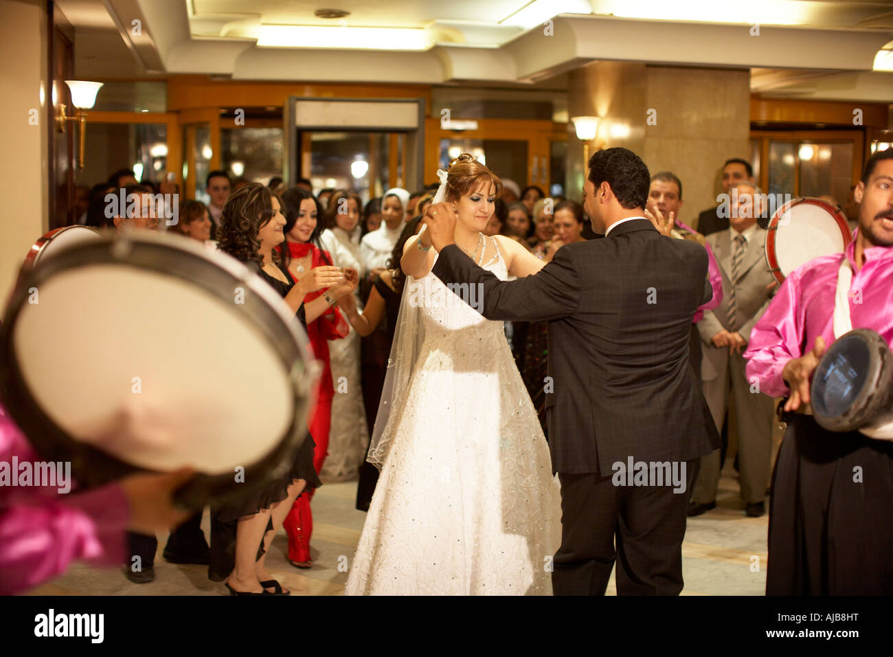 Bride Groom dancing with wedding guests at marriage ceremony party with band playing in hotel lobby Cairo Egypt - Stock Image