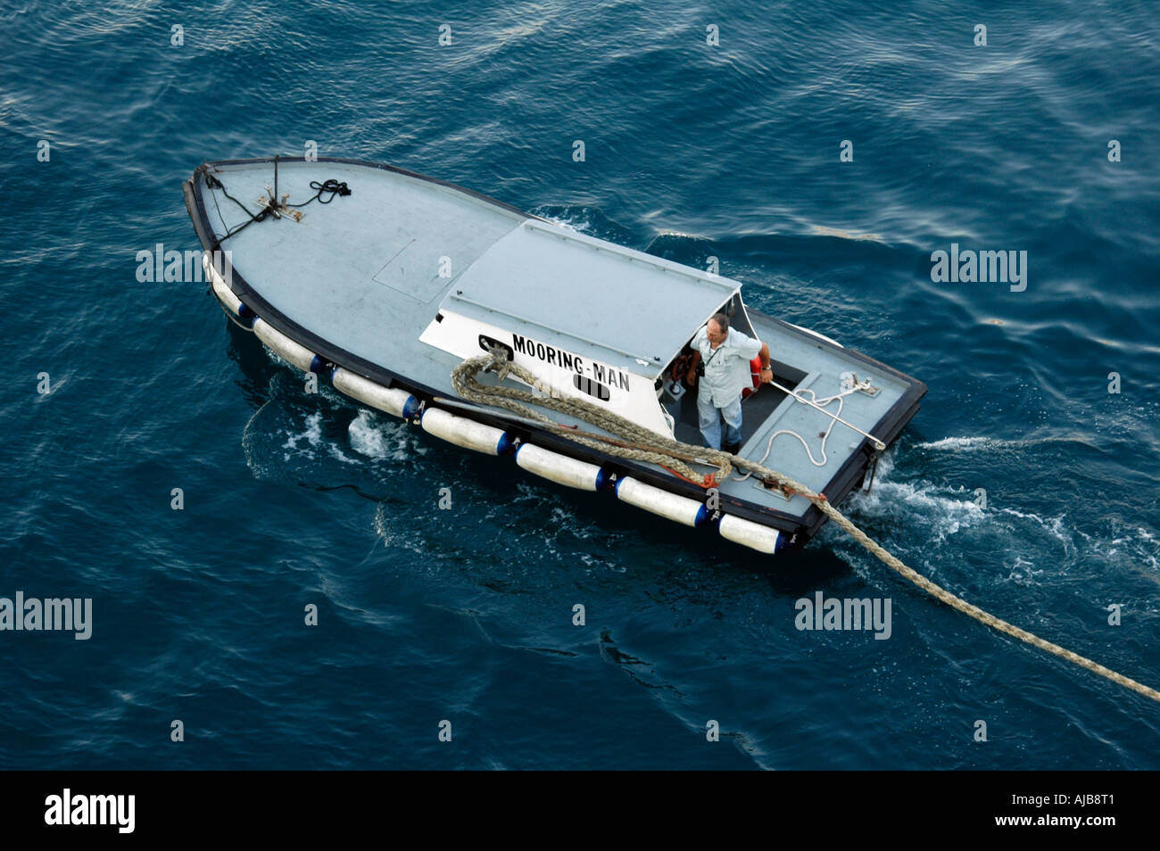 The mooring man boat takes he ropes from the docking vessel to be tied to the wharf port of Messina Sicily Italy July 2006 - Stock Image