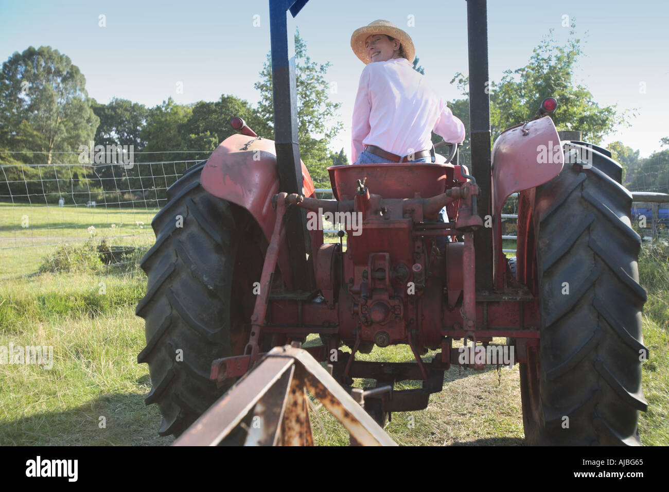 Female tractor driver with straw hat looking over shoulder at Burley Farm - Stock Image