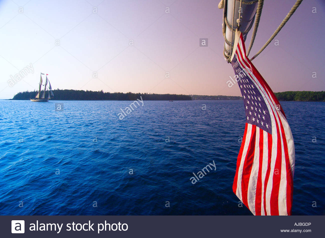 The American flag on the stern of the schooner Nathaniel Bowditch and looking across Holbrook Bay to schooner Mary - Stock Image
