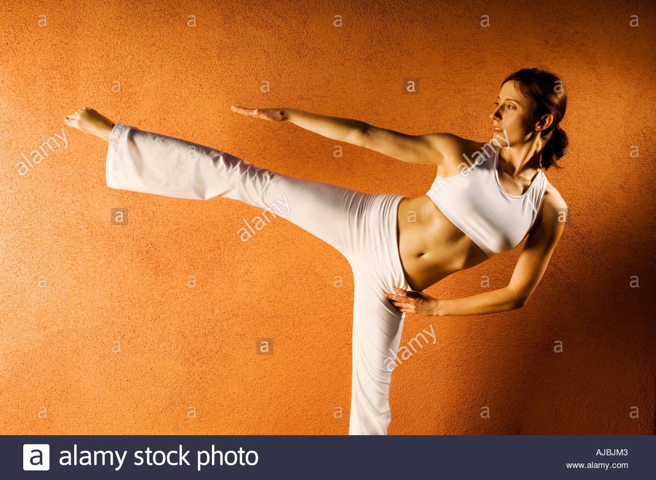 Strong Woman Yoga balance pose with strength beauty balance and grace  in front of Terra-cotta color plaster  wall - Stock Image