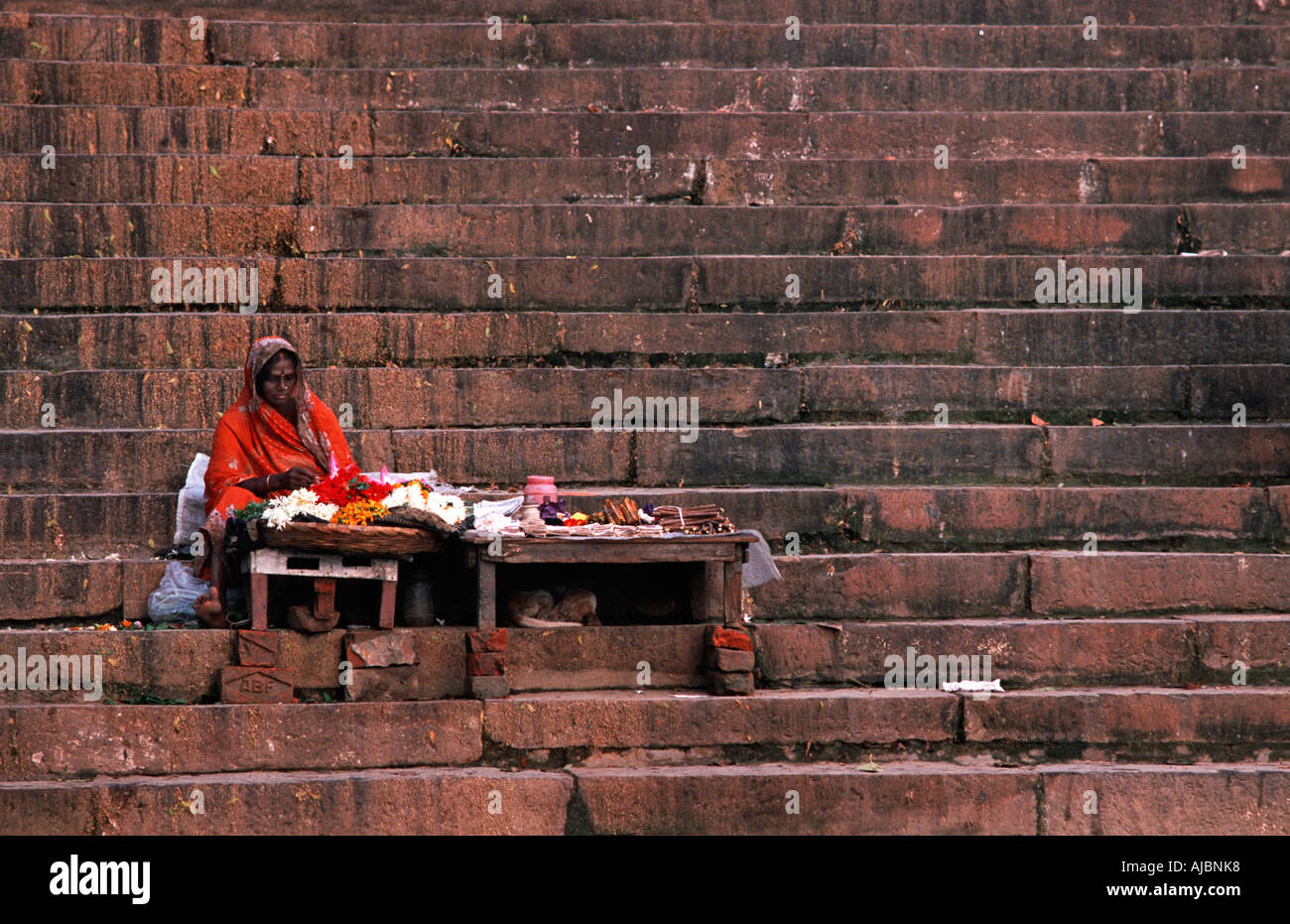 Indian woman vending ritual paraphernalia from a stall on a ghat beside the river Ganges Varanasi India - Stock Image
