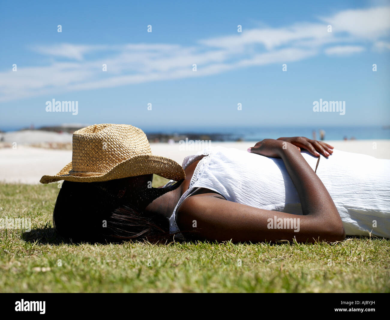 African Woman Sleeping with a Hat Over Her Face - Surface Level - Stock Image