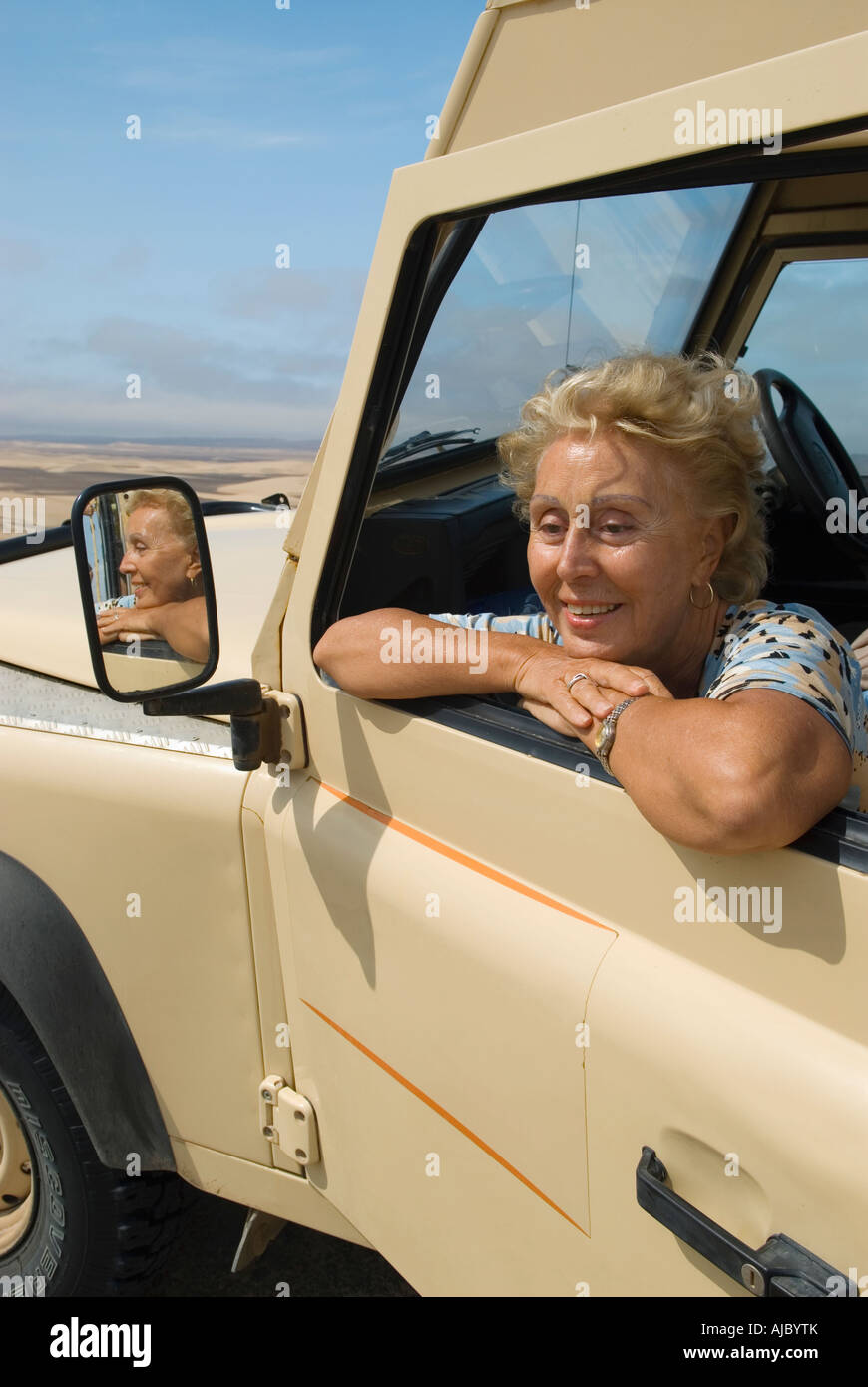 Woman Looking Through the Window of a 4X4 Vehicle - Stock Image