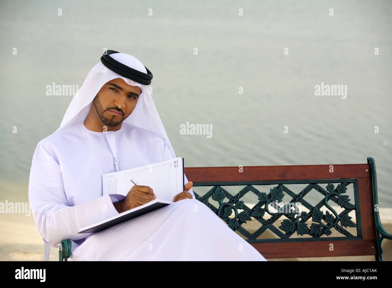 Arab Man Sitting on Park Bench Writing Journal - Stock Image