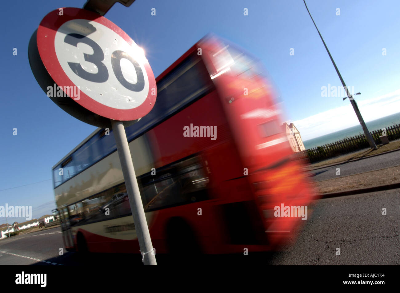 A red double decker bus enters a 30mph zone in the seaside town of Peacehaven - Stock Image